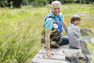 Man fishing with grandson on wooden dock - CAIF01449