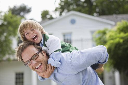 Man carrying son piggyback outdoors - CAIF01452