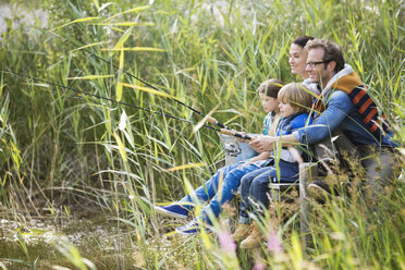 Family fishing together in tall grass - CAIF01455