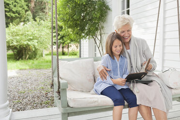 Woman and granddaughter reading on porch swing - CAIF01461