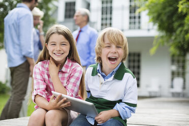 Children using digital tablet together outdoors - CAIF01464