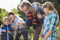 Family admiring fishing catch - CAIF01467
