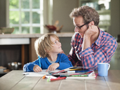 Father and son doing homework at kitchen table - CAIF01479