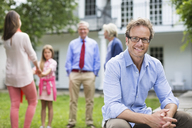 Man smiling outside house - CAIF01482