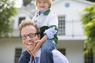 Father carrying son on shoulders outdoors - CAIF01485