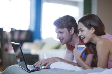 Couple using laptop together on bed - CAIF01518