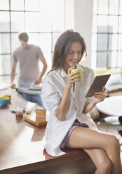 Woman using digital tablet in kitchen - CAIF01536