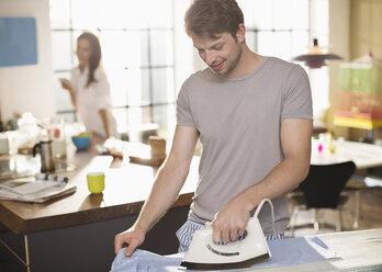 Man ironing shirt in kitchen - CAIF01542
