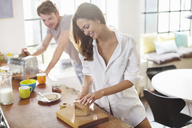 Couple making breakfast in kitchen - CAIF01545