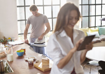 Woman using digital tablet as boyfriend irons in kitchen - CAIF01548