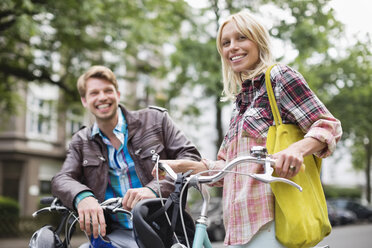 Couple standing on bicycles on city street - CAIF01554
