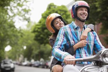 Couple riding scooter together outdoors - CAIF01566