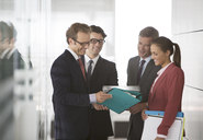 Business people talking in office hallway - CAIF01569