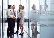 Business people talking in office hallway - CAIF01617