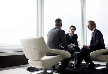 Businessmen talking in office lobby - CAIF01635