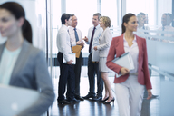 Business people talking in office hallway - CAIF01668