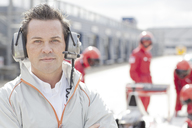 Race manager wearing headphones on track - CAIF01815