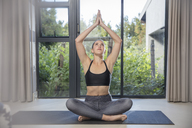 Young woman doing yoga exercise at the window - ZEF15092