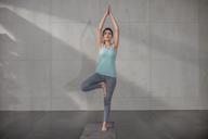 Young woman doing yoga exercise in studio - ZEF15098