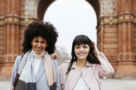 Spain, Barcelona, portrait of two happy women at a gate - EBSF02145