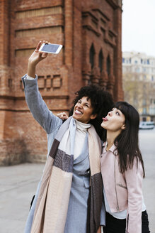 Spain, Barcelona, two playful women taking a selfie at a gate - EBSF02148