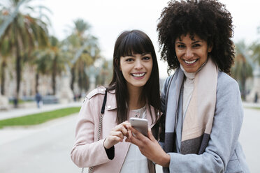 Spain, Barcelona, portrait of two happy women with cell phone on promenade - EBSF02151