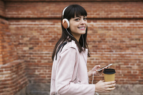 Portrait of smiling woman with coffee, cell phone and headphones at brick wall - EBSF02154