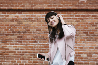 Smiling woman with cell phone listening to music on headphones at brick wall - EBSF02157