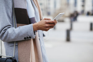 Close-up of woman using cell phone in the city - EBSF02163