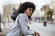 Spain, Barcelona, smiling woman with earphones in the city looking away - EBSF02166