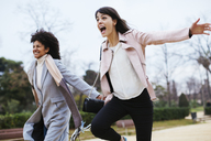 Spain, Barcelona, two exuberant women running in city park - EBSF02178