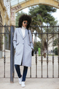 Spain, Barcelona, woman wearing sunglasses standing at a gate - EBSF02181