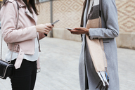 Close-up of two women using cell phones in the city - EBSF02190
