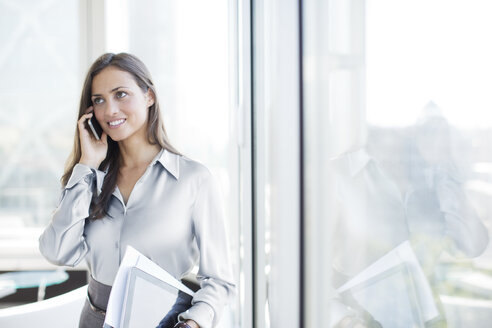 Businesswoman talking on cell phone in office - CAIF01833