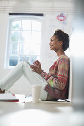 Businesswoman making notes in office - CAIF01836
