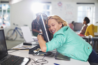 Businesswoman hugging computer at desk - CAIF01839