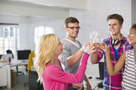 Business people toasting each other with champagne in office - CAIF01851