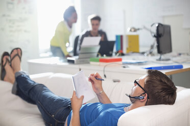 Businessman taking notes on sofa in office - CAIF01857