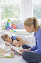 Mother reading to son in bed - CAIF01875