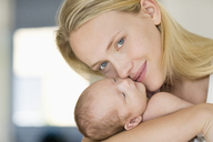 Mother cradling newborn baby - CAIF01887