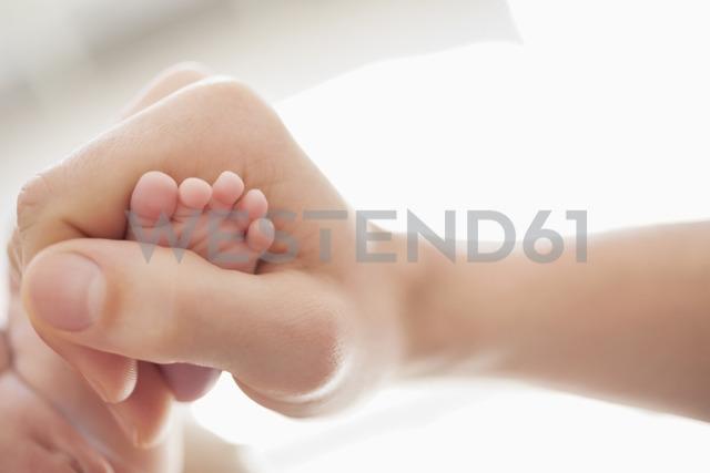 Mother cradling newborn baby's foot - CAIF01902