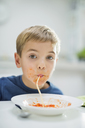 Boy slurping spaghetti at table - CAIF01914
