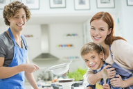 Family cooking together in kitchen - CAIF01938