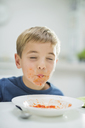 Boy slurping spaghetti at table - CAIF01941