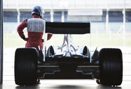 Racer standing with car in garage - CAIF02001