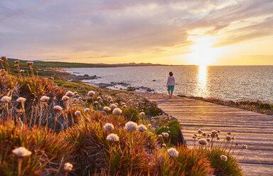 Italy, Sardinia, Lu Litarroni, senior woman on wooden boardwalk at sunset - MRF01890
