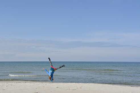 Germany, Pomerania, Hiddensee, girl doing handstand on the beach - BFRF01823
