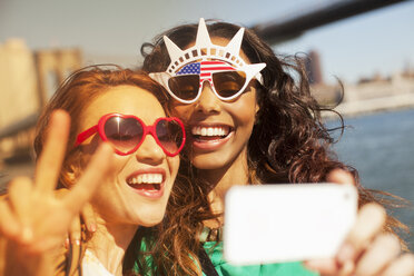 Women taking picture of themselves in novelty sunglasses - CAIF02008