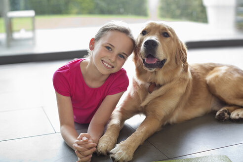 Smiling girl relaxing with dog indoors - CAIF02209