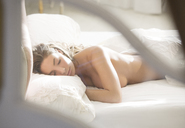 Nude woman sleeping in bed - CAIF02263